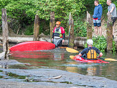 Józefów, Poland - May 12: canoeing, extreme kayaking. The guy in a small sport kayak is practicing with coach how to overcome a difficult obstacle on the Swider River in Poland