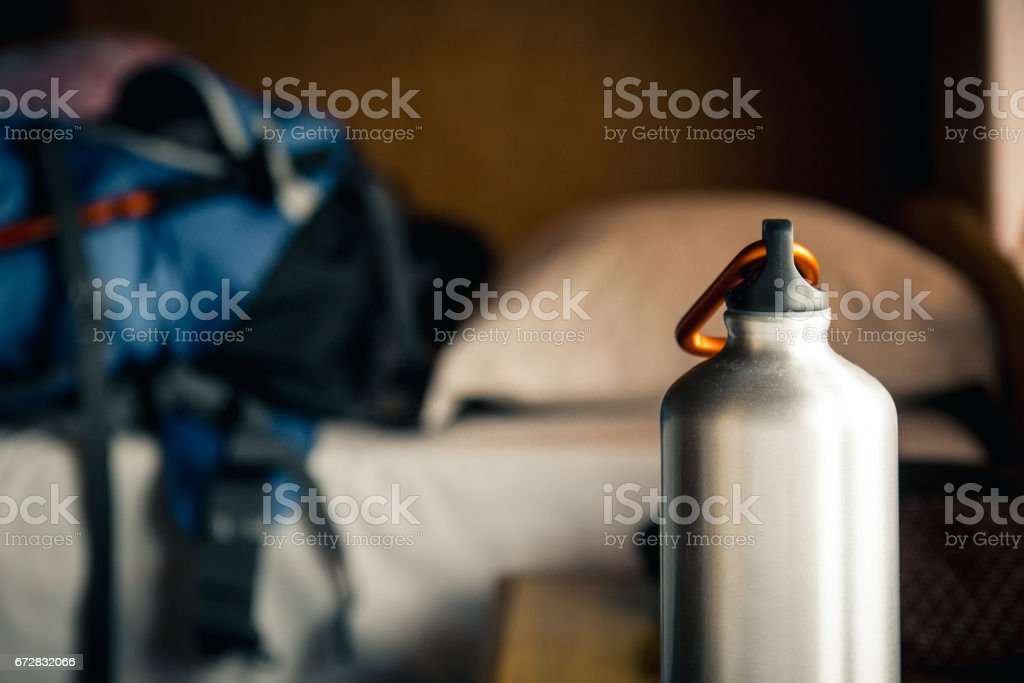 Water canteen used for trekking with some trekking equipment in the background. - foto stock