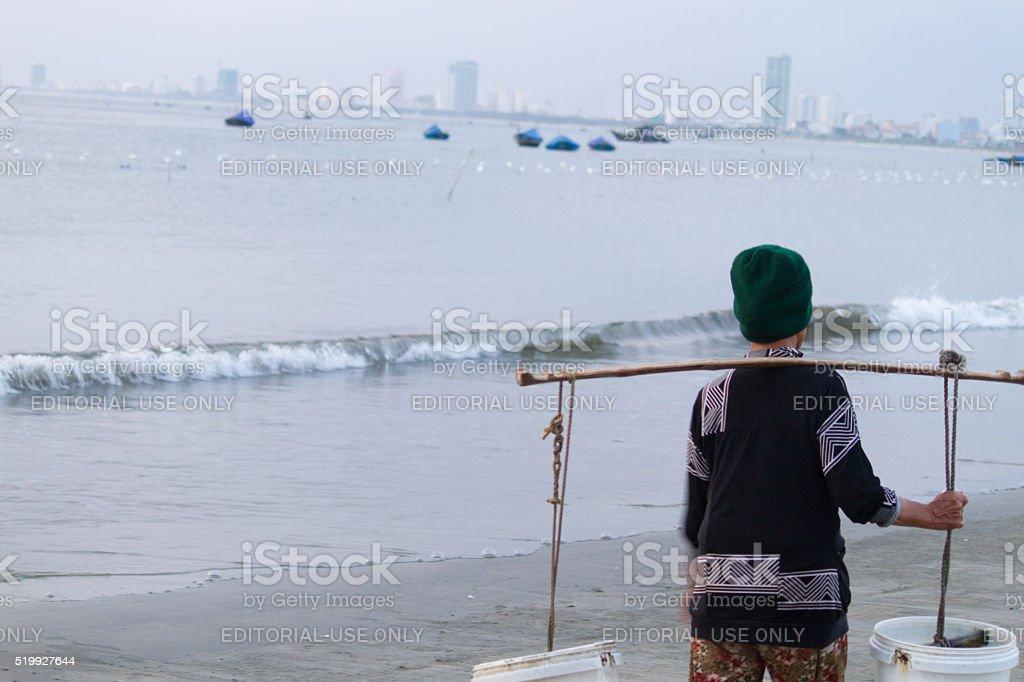 Water carrier woman & boats at dawn, Danang beach, Vietnam stock photo