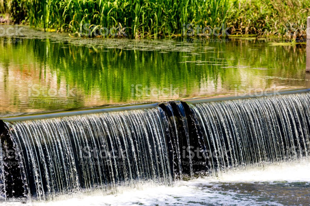 Water cascade streaming down from small dam, water saving ecology...