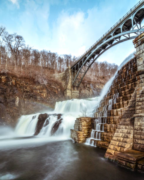 Water cascading down New Croton dam with a bridge arching over the waterfall