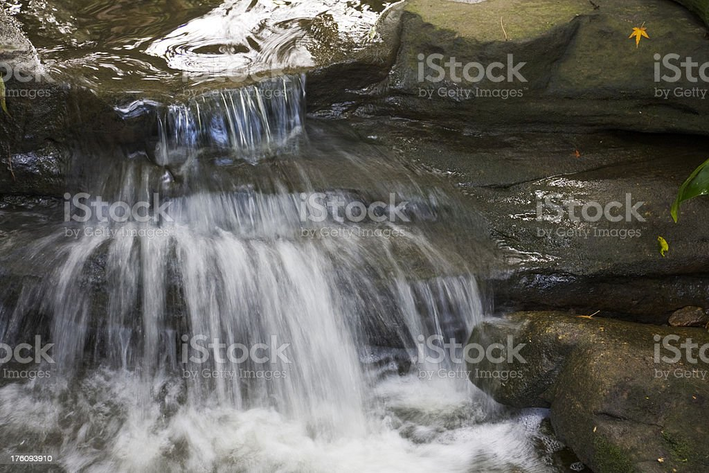 Water cascading over rocks of a small stream stock photo