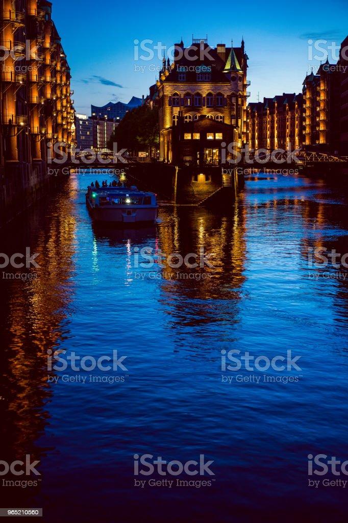 Water castle in old Speicherstadt or Warehouse district, tourist boat on a channel. Hamburg, Germany zbiór zdjęć royalty-free