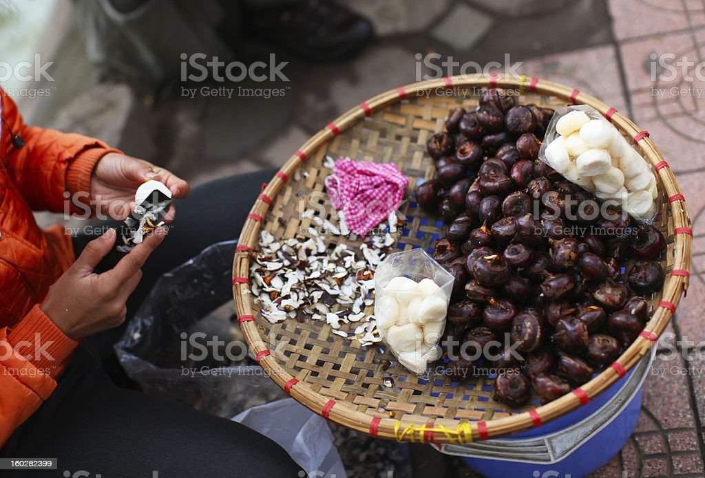 Water chestnuts being peeled at the market in Asia stock photo