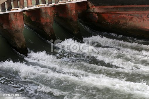 Water running rapidly under dam in river.