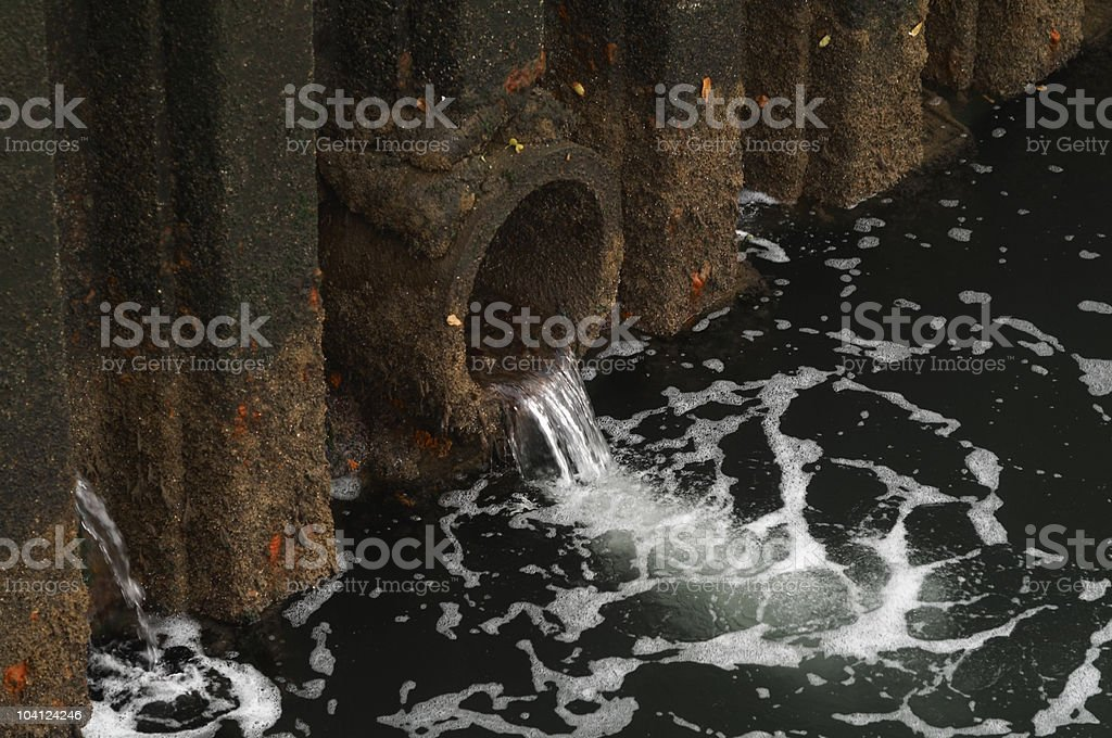 Water discharge. Water flowing out of a large pipe stock photo