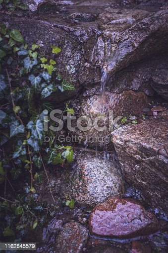 Water dripping over stones in a small stream in the mountains in the evening