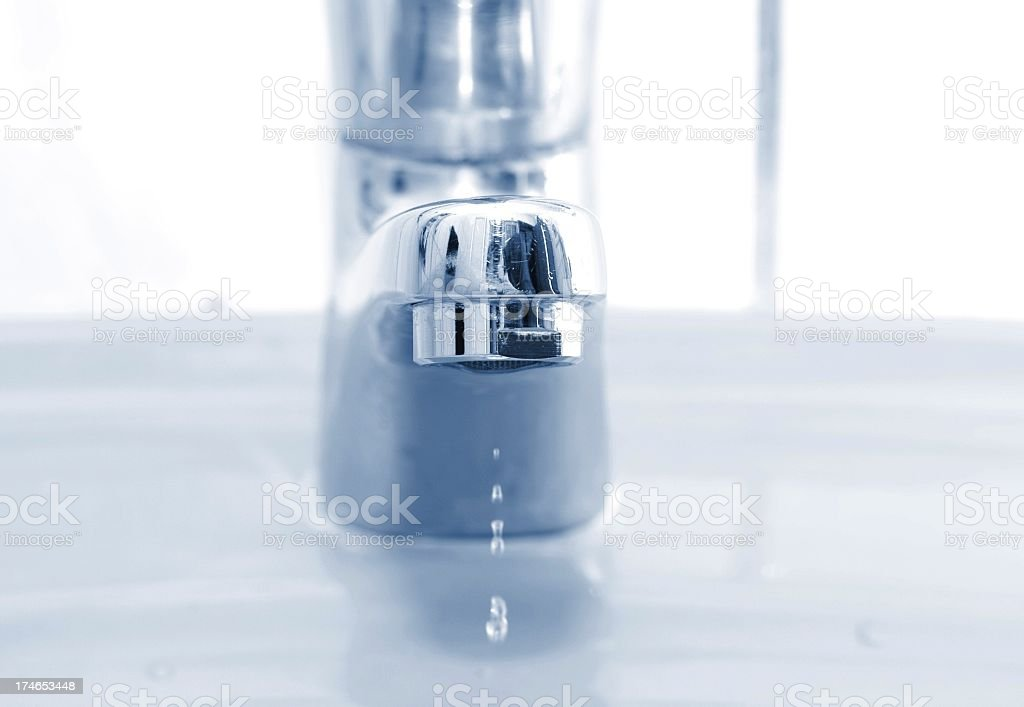 water drips out of a silver faucet royalty-free stock photo