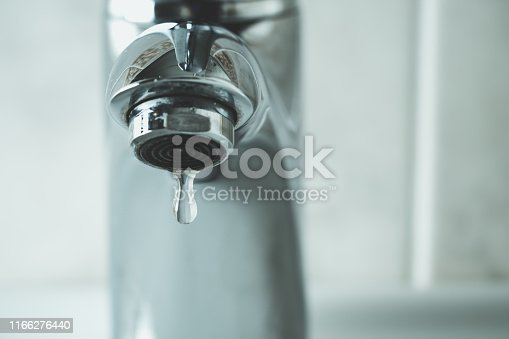 water drop dripping from the tap and water shortage