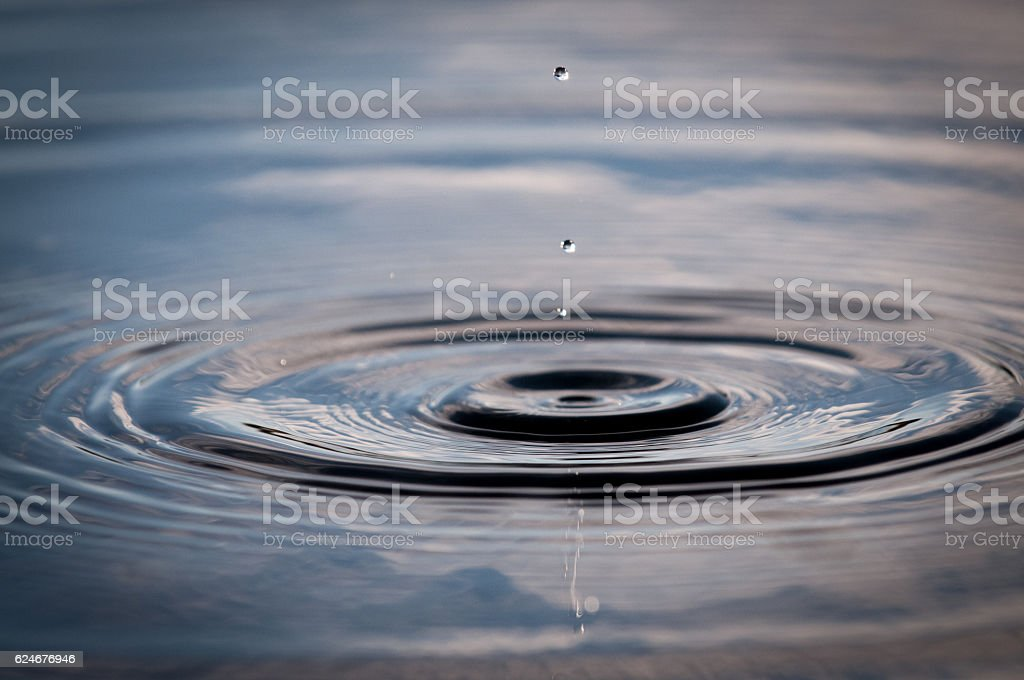 Water Drop Falling Onto The Surface Of A Pond stock photo
