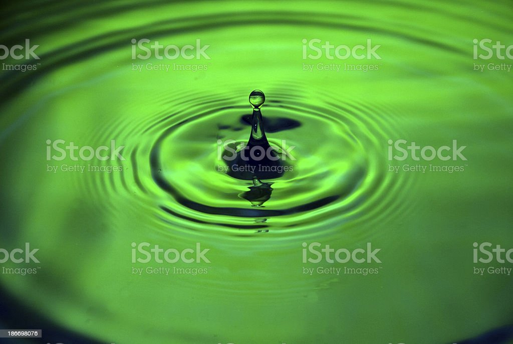 Water drop into a pool of green royalty-free stock photo