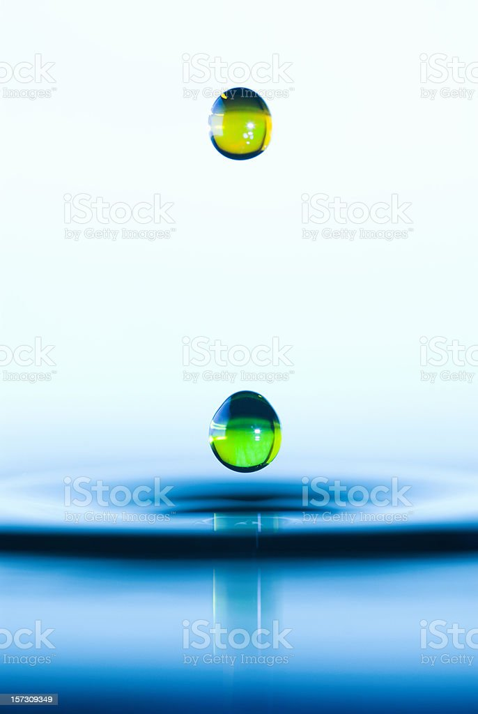 Water Drop Splash as it Hits Water Surface stock photo