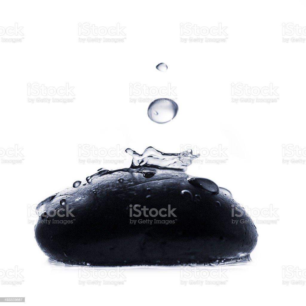 water drop splashing on pebble stock photo