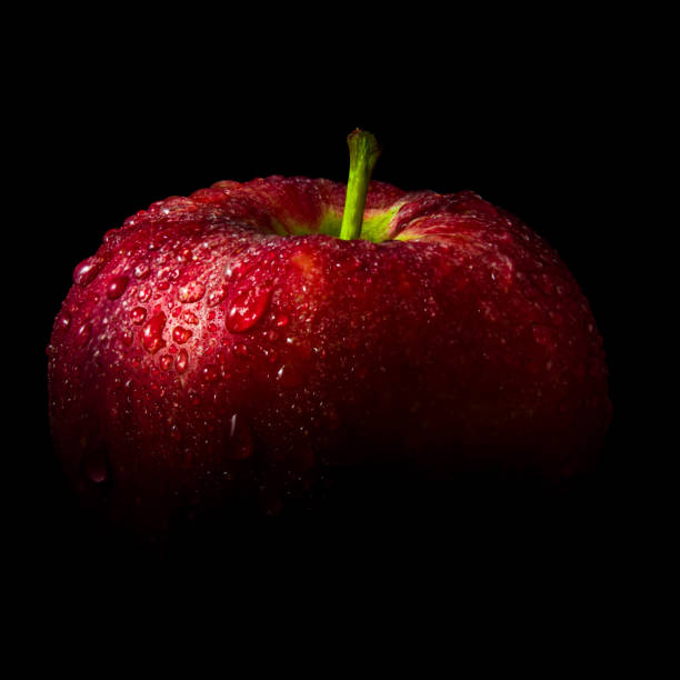 Water droplet on glossy surface of red apple on black background stock photo
