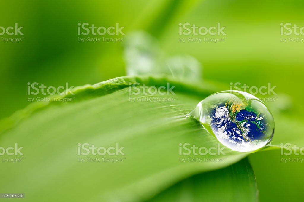 Water droplet with Earth reflection resting on a green leaf stock photo