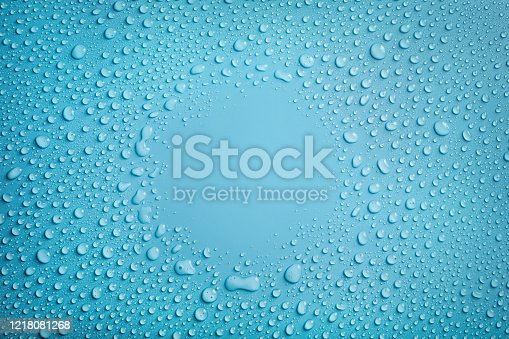 Circle frame of water drops on blue background. Copy space