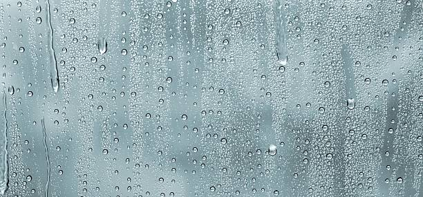 water drops on a window - condensation stock photos and pictures