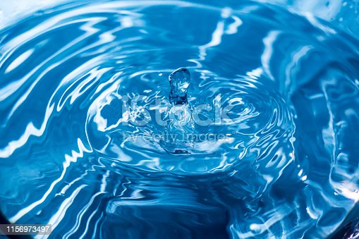 607461154istockphoto Water drops on blue surface. Water ripple background. Splashes from a drop of water. Raindrops on a blue background. The texture of the water. Aqua, turquoise, macro 1156973497