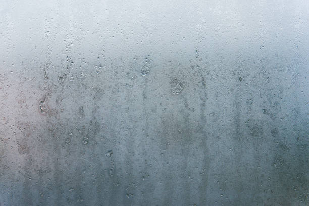 water drops on window glass - condensation stock photos and pictures