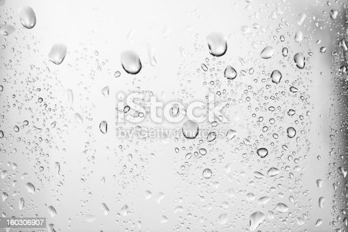 Water droplets on glass in front of a white background.  Various sizes of water droplets from large to very small rest on the front of a glass.  The droplets near the top of the image are larger and more visible than the droplets near the bottom and to the sides.  The larger droplets have slight shadowing to them which gives the drops an added depth and texture.  The very top of the image has no droplets.  The white background is a gradient with darker edges on the sides and an almost black edge on the right.