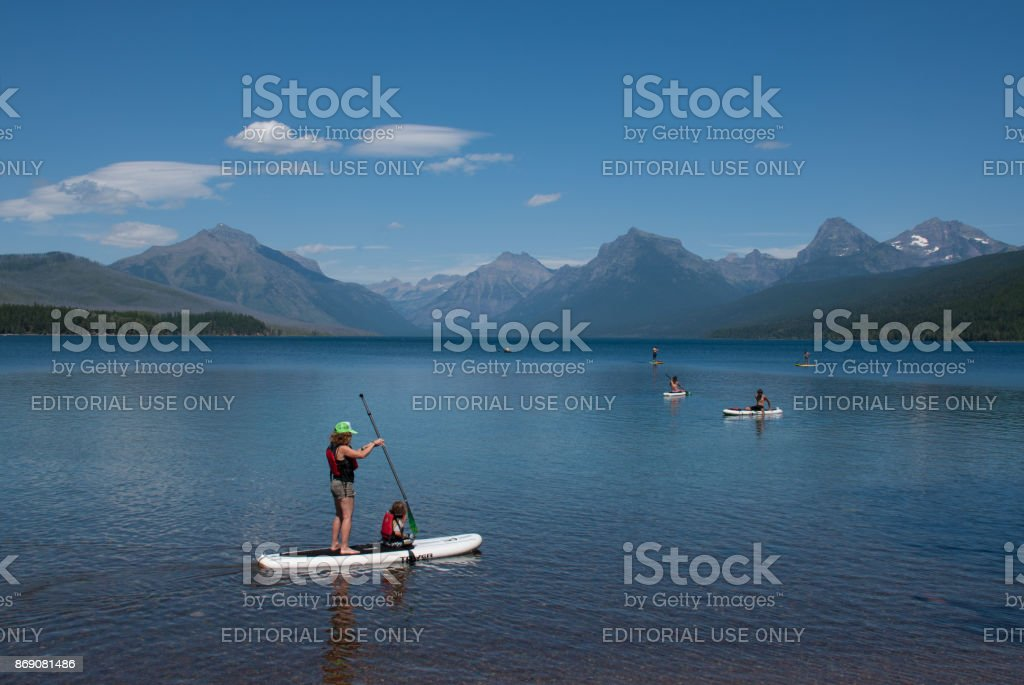 Water enthusiasts enjoy Lake McDonald in Glacier National Park stock photo