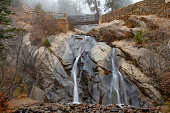 Hellen Hunt water fall in Colorado Springs Colorado USA. Unusual thick daytime fog on cold late autumn day. Long exposure.