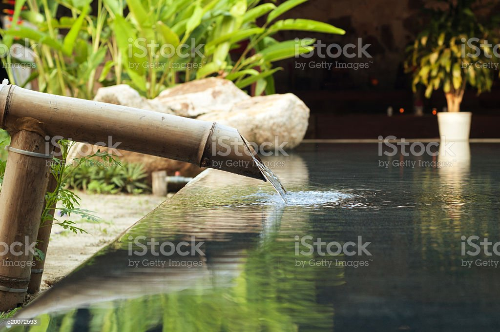 water falling down from bamboo pipe stock photo