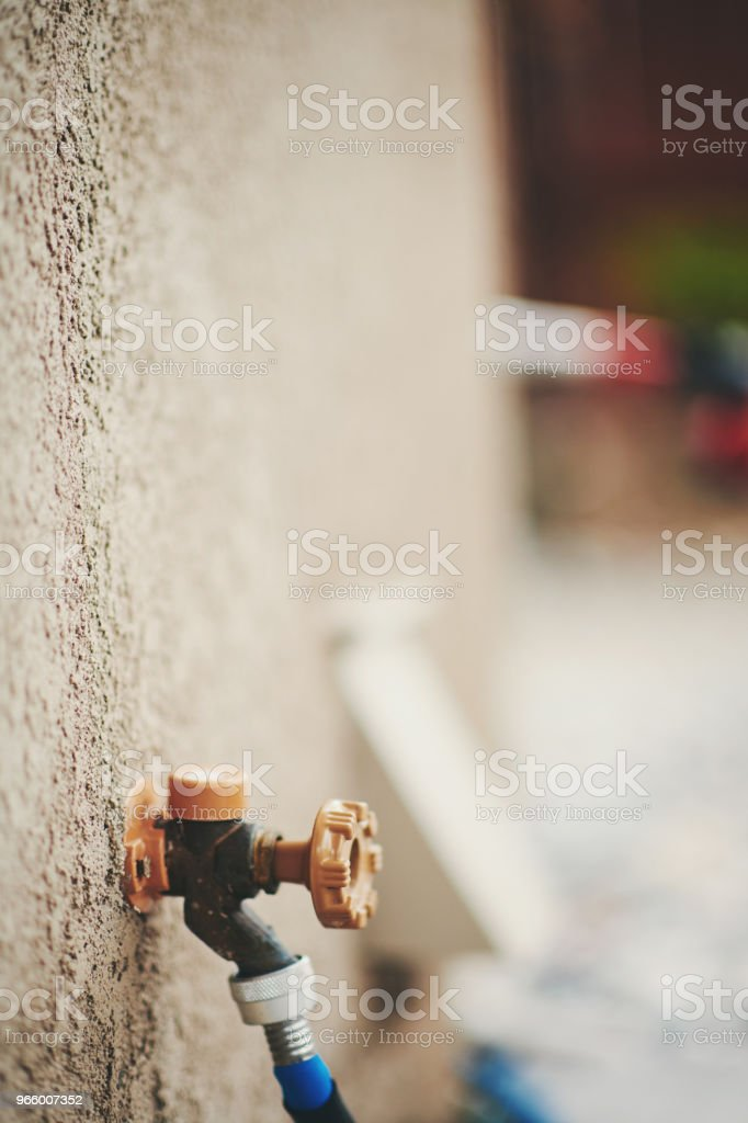 Water faucet with garden hose in residential garden - Стоковые фото Американская культура роялти-фри