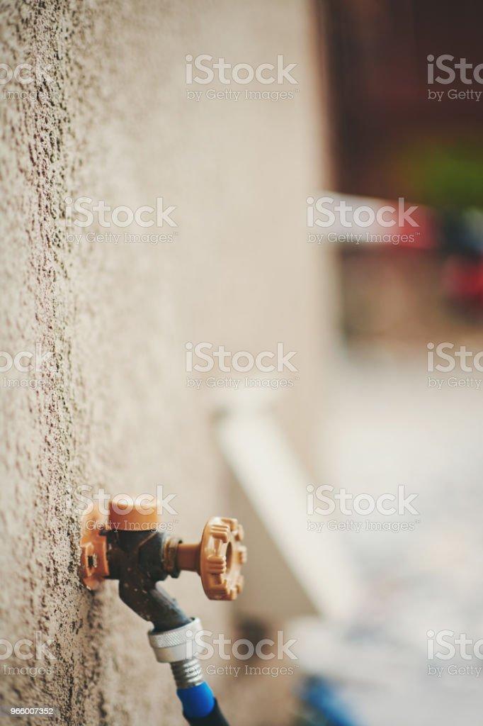 Vattenkran med trädgårdsslang i bostadsområdet trädgård - Royaltyfri Amerikansk kultur Bildbanksbilder