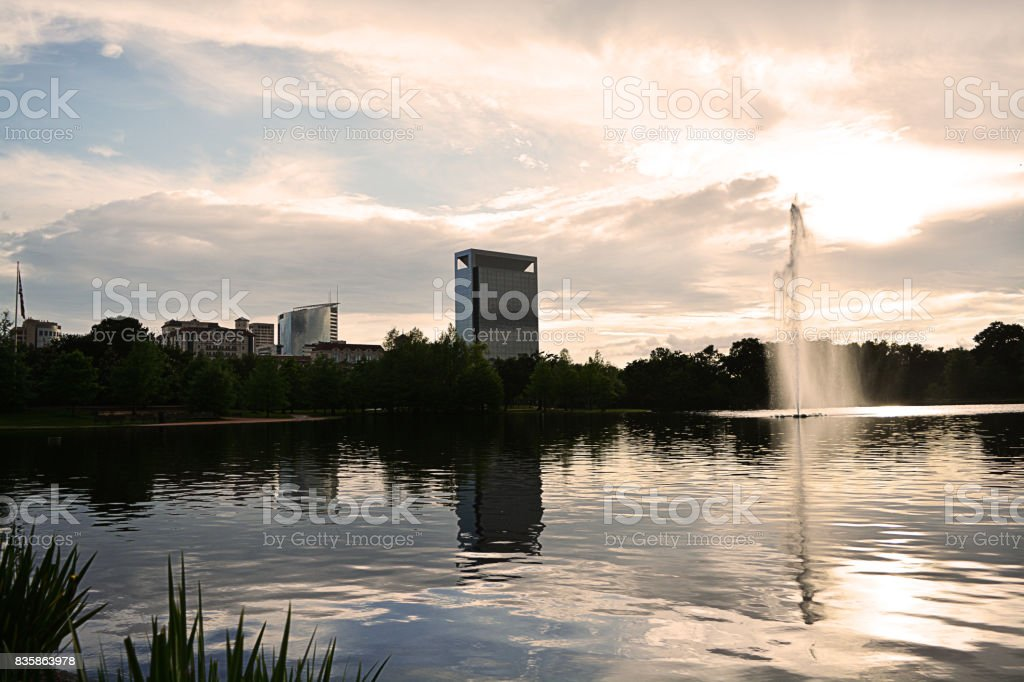 Water feature at the park with deep reflections of the cityscape in the background stock photo