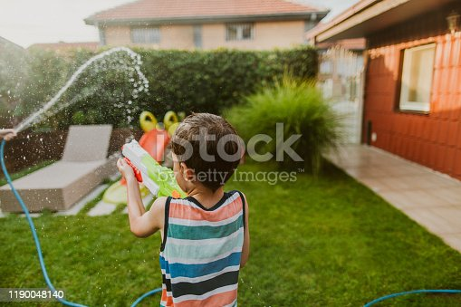 Photo of little boy during the water fight in the yard
