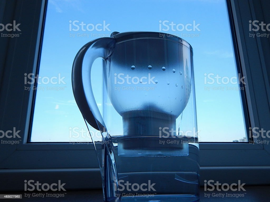 Water filter jug with clear water at kitchen stock photo