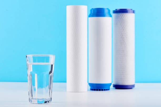 Wasserfilter. CO2-Patronen und ein Glas auf einem weißen blauen Hintergrund. Haushalt-Filtersystem. – Foto