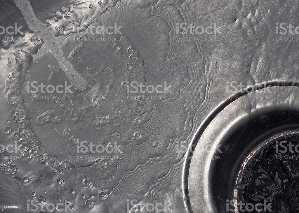 Water flow running down kitchen drain stock photo