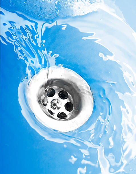 wasser fließt down the drain-englische redewendung - kuqa stock-fotos und bilder