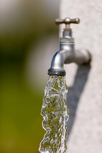 water flowing from faucet - çeşme i̇nsan yapımı yapı stok fotoğraflar ve resimler