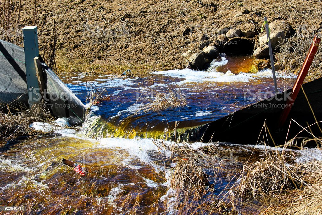Water flowing out of a culvert in spring royalty-free stock photo