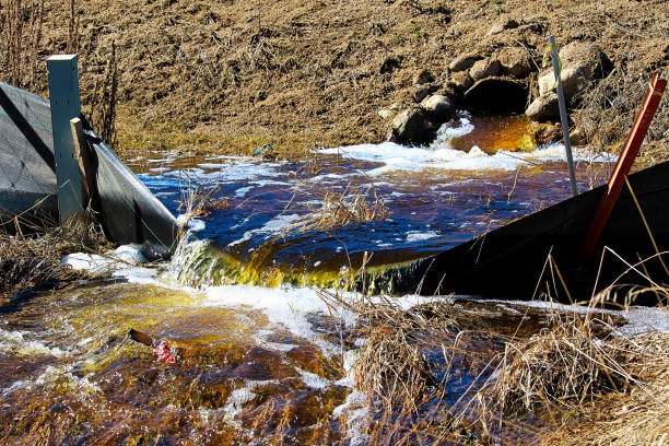 Water flowing out of a culvert in spring stock photo
