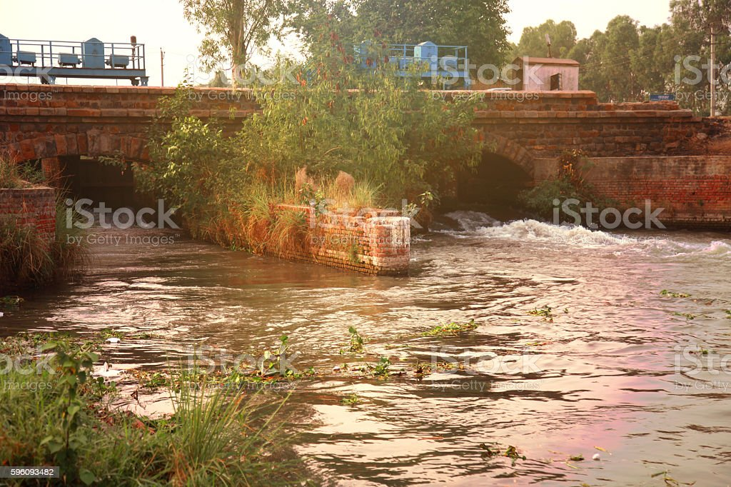 Water flowing through a dam with a bridge above royalty-free stock photo