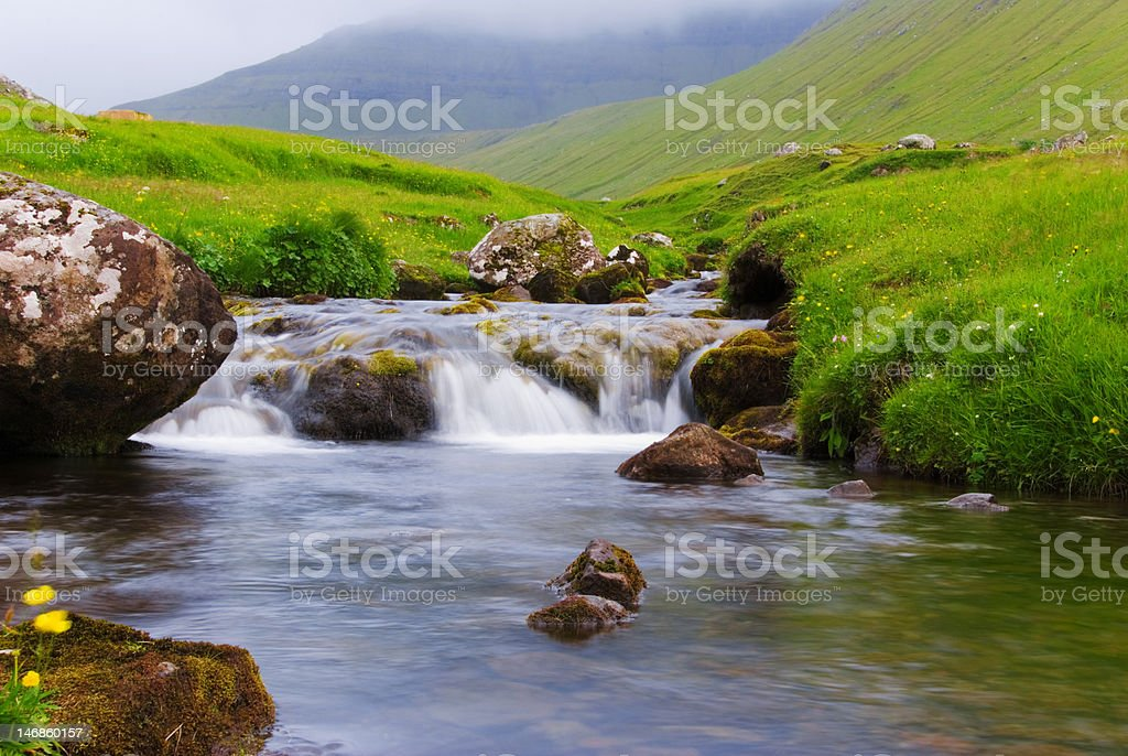 Water flows between moss rocks royalty-free stock photo