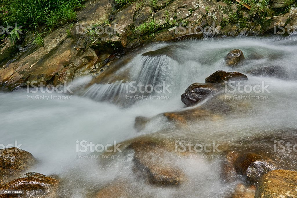 Water flows over rocks in a little waterfall. foto royalty-free