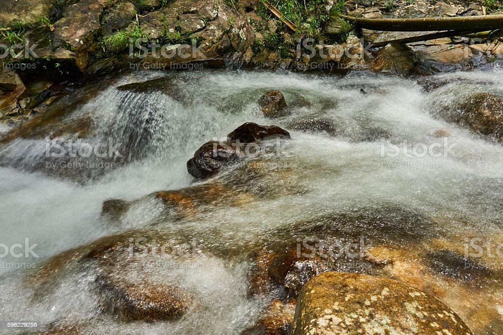 Water flows over rocks in a little waterfall. foto royalty-free
