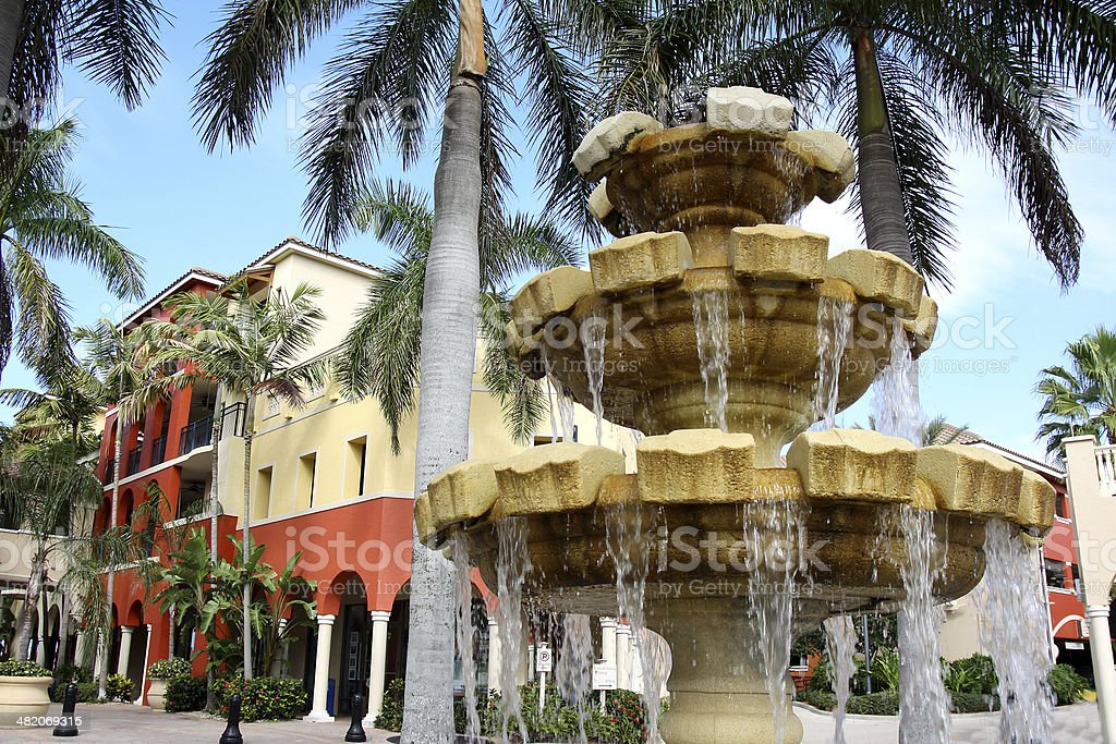 Water Fountain in Front of Colorful Building and Palm Trees stock photo