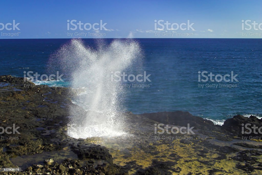 Water from the ocean being sprayed out of the Spouting Horn, an old volcanic lava tube on the island of Kauai in Hawaii. stock photo