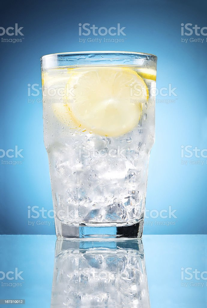 Water glass with lemon and ice isolated on blue background royalty-free stock photo