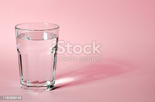 Glass beaker from which padajet sharp shadow, stands on a pink background. Empty space for text