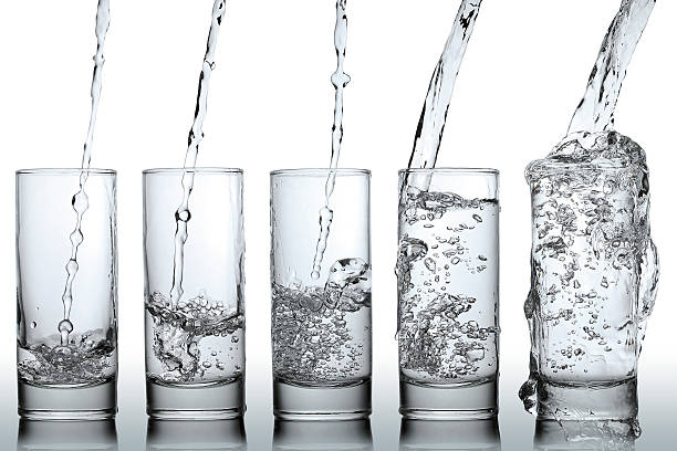 Water going in series of glasses to illustrate empty to full stock photo