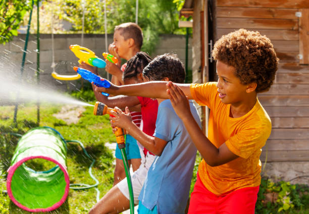 Water gun fight game with many kids in action stock photo