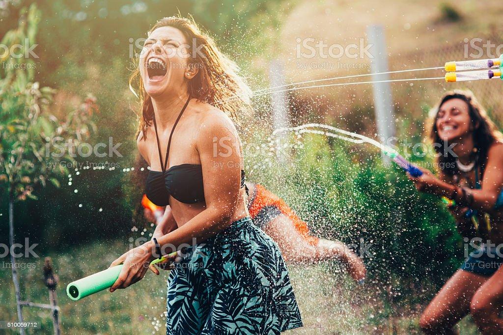 Water Gun Fight A girls gets shot by a water gun. 20-29 Years Stock Photo