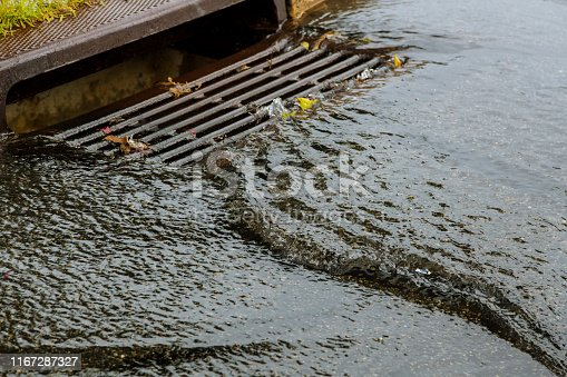 Water gushing from storm sewer following very heavy rainfall of the road after heavy rain.